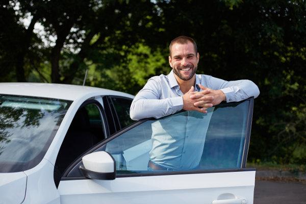 sebevědomý muž stojí u svého luxusního vozu