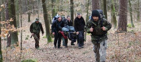 účastníci kurzu přežití v přírodě zachraňují kamaráda