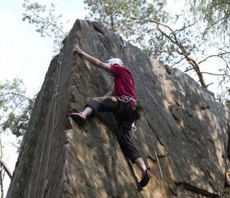 účastník kurzu lezení při výstupu na skálu
