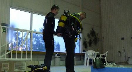 instruktor obléká účastníka kurzu potápění