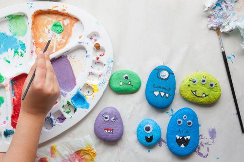 malíř namáčí štětec do barvy a maluje na kameny