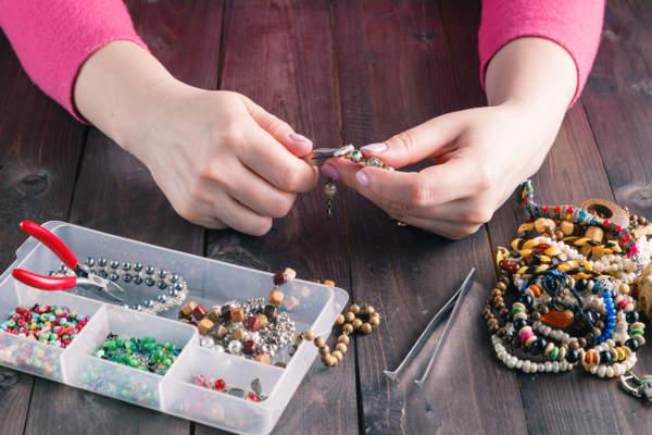 žena ketluje a vyrábí náramek technikou korálkování