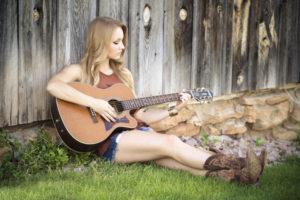Fotografie ženy která hraje na kytaru