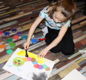 Fotografie holčičky jak maluje obrázek z písku