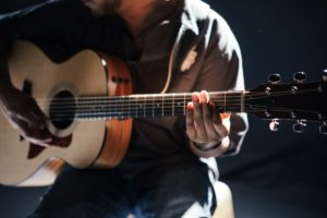 Fotografe kytaristy jak hraje na kytaru.