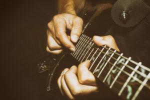 fotografie mužských rukou jak hrají na kytaru a stiskem strun vytváří akord