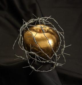 Fotografie zlatého jablka a drátu omotaného kolem něj.
