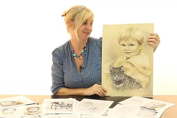 Fotografie pani která drží v ruce nakreslený obrázek dítěte