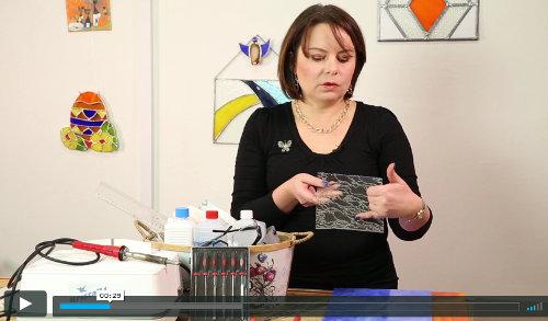 lektorka na videu ukazuje pomůcky potřebné pro tvorbu výrobků technikou tiffany vitráže