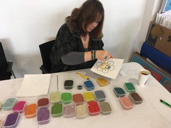 paní tvoří obrázek pomocí barevného písku na tvořivém workshopu