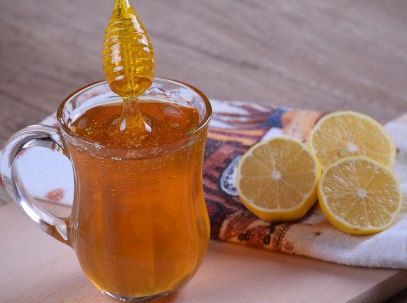 lžíce namočená do domácího rýmovníkového medu ve sklenici. Na stole leží citrón