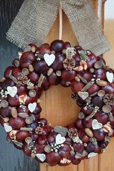 na dvěřích je zavěšený veliký věnec vyrobený z kaštanů, žaludů a sušených podzimních plodů