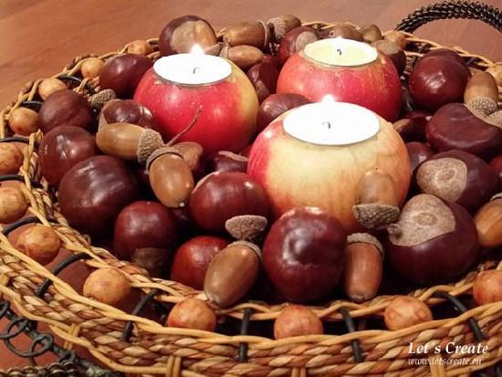 v ošatce leží kaštany a žaludy a uprostřed jsou tři svíčky vložené do jablka