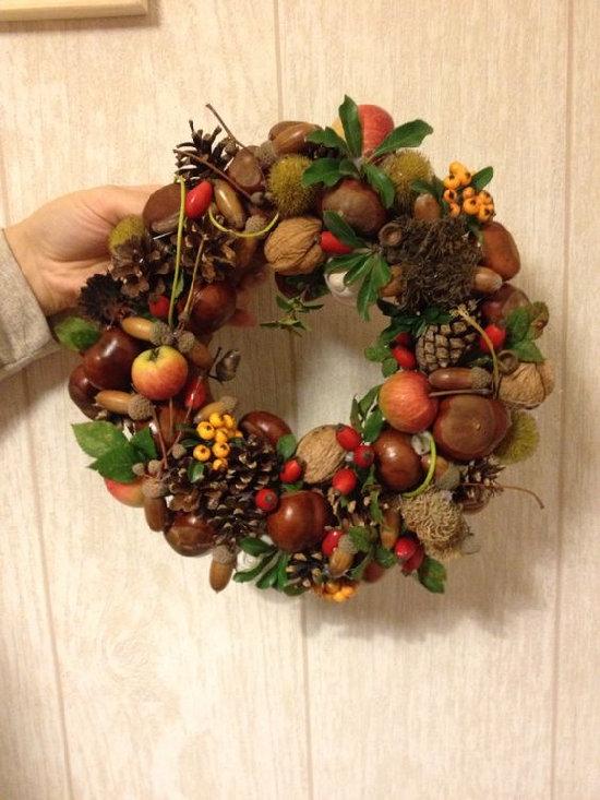 na dvěřích visí kulatý věnec z kaštanů, šípků a dalších podzimních rostlin