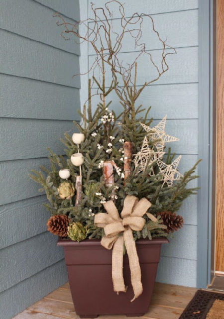 hnědý truhlík vánočně vyzdobený větvičkami, šiškami a hnědými hvězdičkami