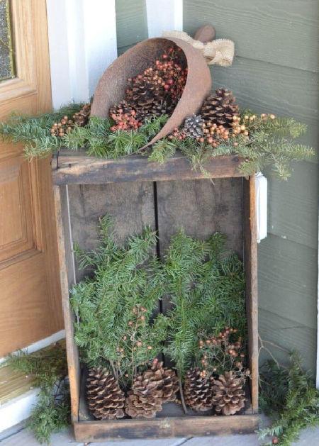 dřevěná bedýnka plná šišek a jehličnatých větviček