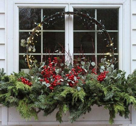 Vánoční truhlík na okně plný červených bobulí a světýlek