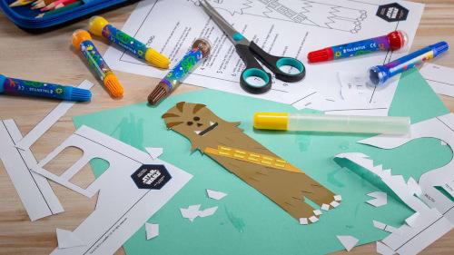 pastelky, nůžky, papír a výsledná vyrobená knižní záložka