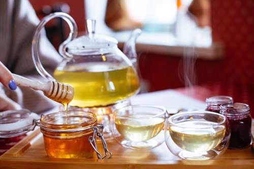 na stole stojí bylinné čaje, nádobka s medem a skleněná konvice