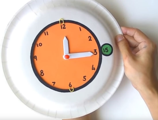 rodič drží v ruce papírové hodiny a řeší jak naučit děti hodiny