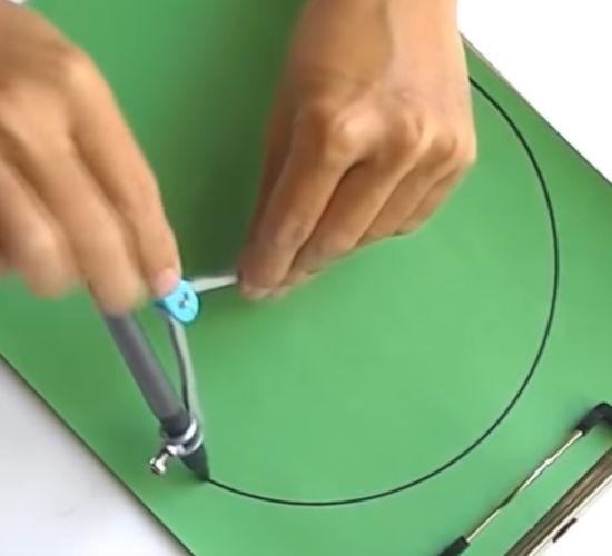 lidské ruce dělají kružnici na zeleném papíru pomocí kružítka