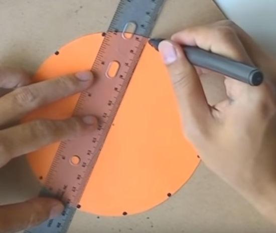 na stole leží kruh z oranžového papíru na který ruce pomocí pravítka fixu malují tečky
