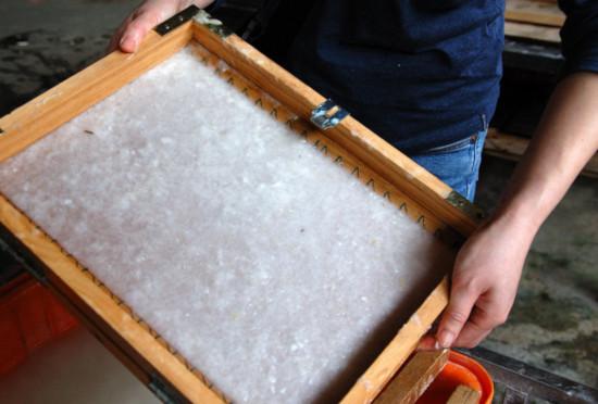 v dřevěném rámečku je ručně vyrobený papír