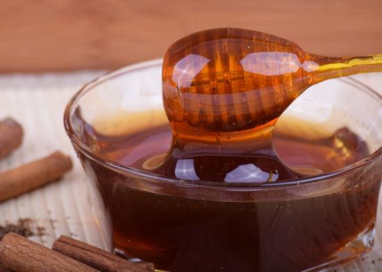na dřevěné lžičce je med, který bude použit na přípravu homemade pleťové masky