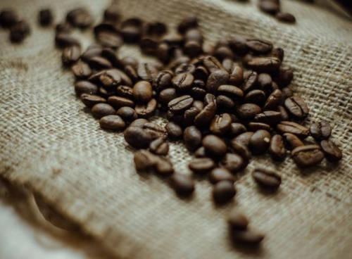 zrníčka kávy leží na jutovém pytli a čekají na pomletí jako přísada do domácí vlasové masky