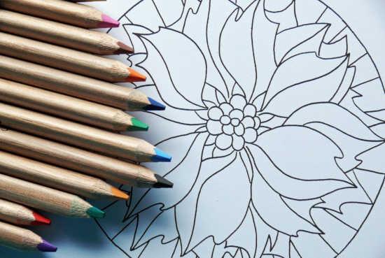 barevné pastelky leží na relaxačních omalovánkách pro dospělé