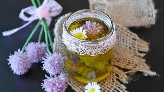 na stole leží sklenice plná domácího DIY bylinkového oleje s květinami