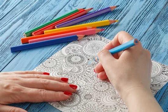 na stole leží barevné pastelky a ženské ruce malují omalovánky proti stresu