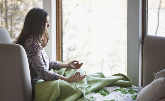 žena sedí na sedačce v obýváku a učí se meditovat