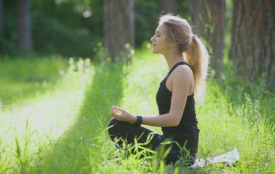 žena v lotosém sedu v lese medituje