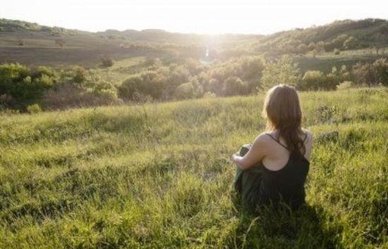žena sedí na louce a medituje při pohledu na krajinu zalitou sluncem