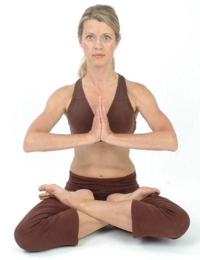 paní v hnědém oblečení sedí při meditaci v lotosovém sedu