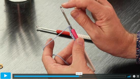 lektor ukazuje ve video návodu na háček při háčkování
