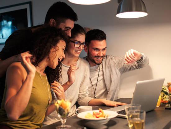 kamarádi se u notebooku baví hraním online hospodským kvízem