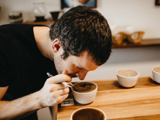 Znalec kávy se naklání nad šálek lahodné kávy a čichá její vůni - účastník domácího online video kurzu přípravy kávy