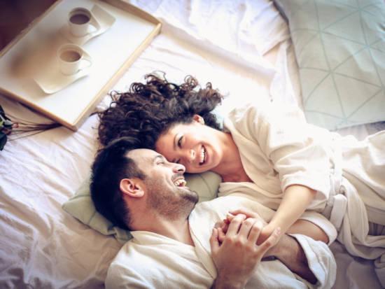 Štastný pár (muž a žena) leží v posteli a smějí se spolu - absolvovali online kurz tajemství štastného vztahu