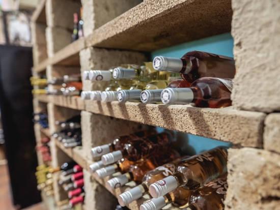 láhve vína leží v regálech - určeno pro zážitkovou domácí online degustaci vína