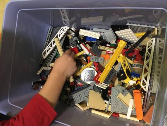 Plný box LEGO kostiček na váhu a z setů, ve které se přehrabuje dětská ruka