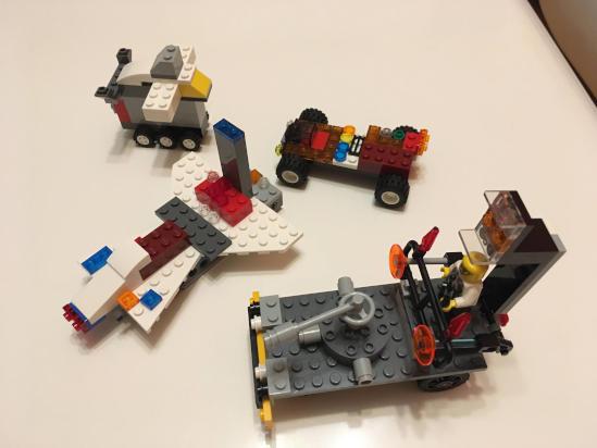 Čtyři LEGO auta stojí na stole. Jsou postavená dětmi bez návodu dle představivosti a fantazie