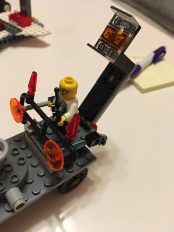 postavička (figurka) z lega řídí dětmi postavené auto