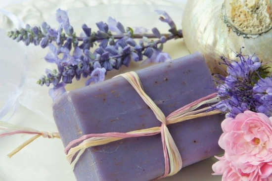 snítka levandule je položená vedle doma vyrobeného bylinkového mýdla