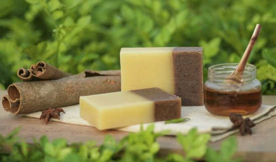 na stole leží doma vyrobené mýdlo, vedle něj leží sklenice s medem a skořice