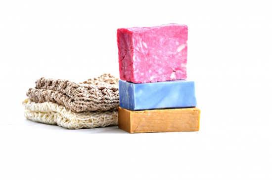 různobarevná bylinková mýdla domácí výroby leží na sobě a vedle nich leží přírodní obal na mýdlo