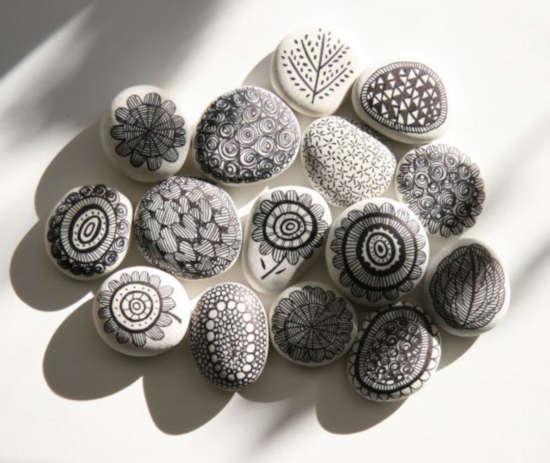 na bílém papíru leží kameny pomalované černou tuší