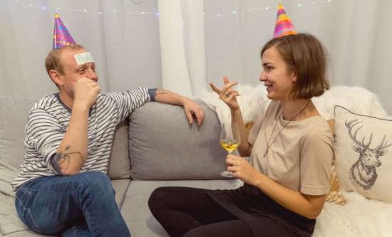 dva lidi sedí na sedačce a hrají párty hru hádání známé osobnosti
